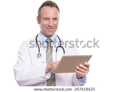Professional male doctor in a white coat standing consulting a tablet computer reading the information with a friendly expression, isolated on white - stock photo