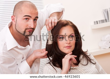 Professional male hairdresser choose hair dye color at modern salon, female customer change hair color - stock photo