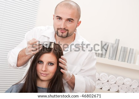 Professional male hairdresser color female customer at design salon - stock photo