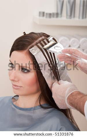 Professional male hairdresser color female customer at design salon, creating highlights - stock photo