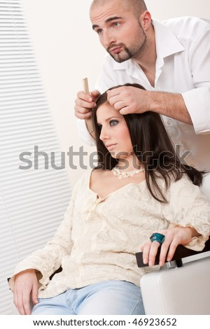 Professional male hairdresser comb female customer at salon, looking into mirror