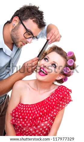 Professional male hairdresser making a hairstyle from blond woman, isolated on white - stock photo