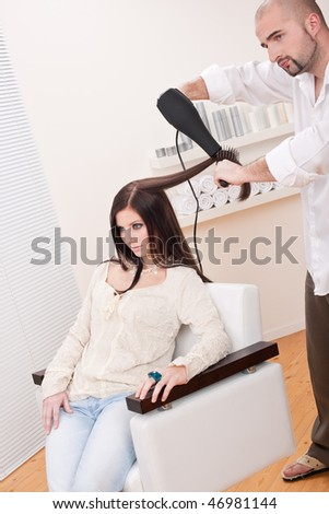 Professional male hairdresser with hair dryer and hair brush drying hair at salon with female customer