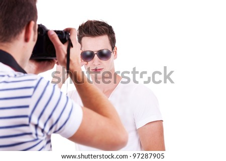 professional male photographer taking a picture of his male model on white background - stock photo