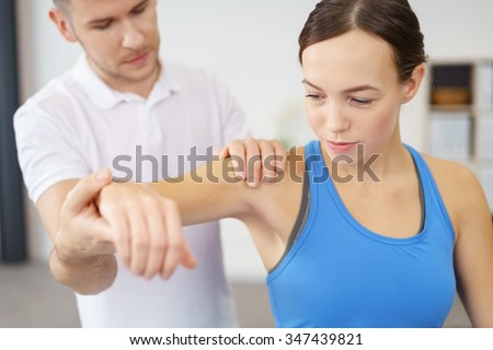 Professional Male Physical Therapist Helping his Female Patient in Exercising the Injured Shoulder. - stock photo