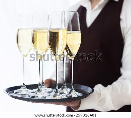Professional male waiter in uniform serving champagne. DOF. Natural light. Photo in motion - stock photo