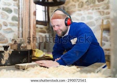 Professional male woodworker in a blue uniform is cutting plank of wood on a power-saw bench - stock photo