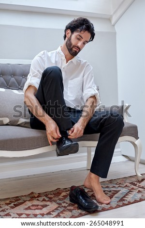professional man getting ready for work putting smart shoes on and tying shoelaces at home - stock photo