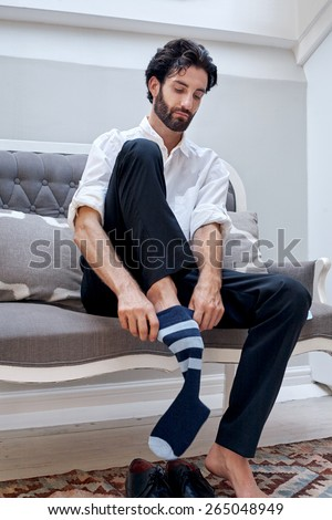 professional man getting ready for work putting socks for work in morning at home - stock photo