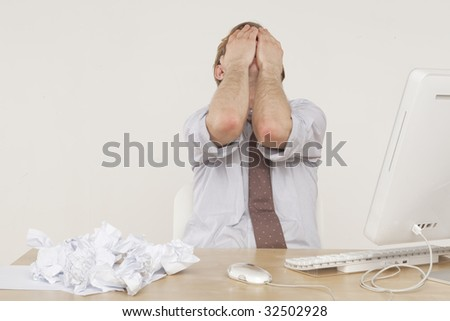 professional man sitting at desk with face in hands - stock photo