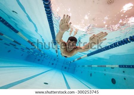 Professional man swimmer inside swimming pool. Underwater image. - stock photo