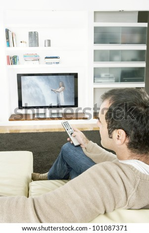 Professional man using a tv remote control to change channels on the television at home. - stock photo