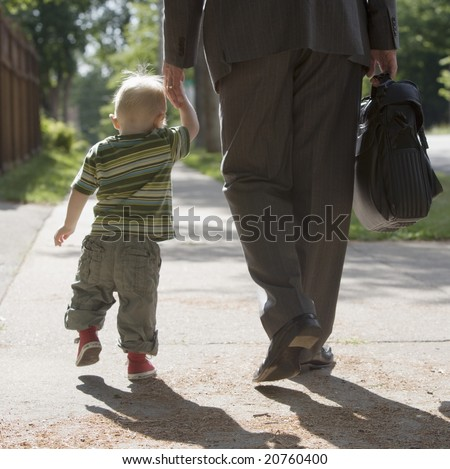Professional man walking his child to school or daycare - stock photo