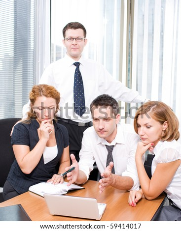 Professional manager trying to explain his office workers new business strategy in board room Hi Res. People looking at the laptop computer's screen and listening to him very attentively. - stock photo