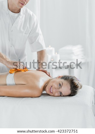 Professional masseur and content woman during massage, light interior