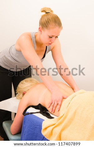 Professional masseur doing massage of female back - stock photo