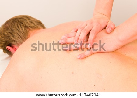 Professional masseur doing massage of male back - stock photo