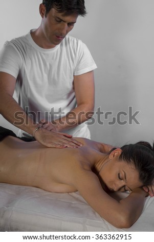 Professional masseur doing massage on woman body in the spa salon. Beauty treatment concept. - stock photo
