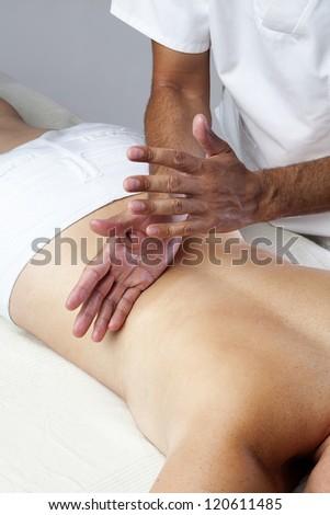 Professional Masseuse Giving a Back Massage - stock photo