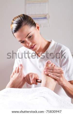 professional masseuse giving foot massage
