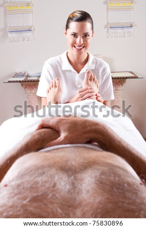 professional masseuse giving foot massage to male customer