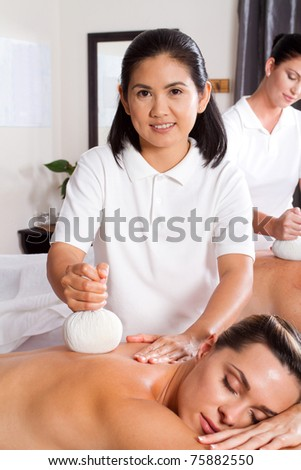 professional masseuse giving Thai herbal compress massage - stock photo