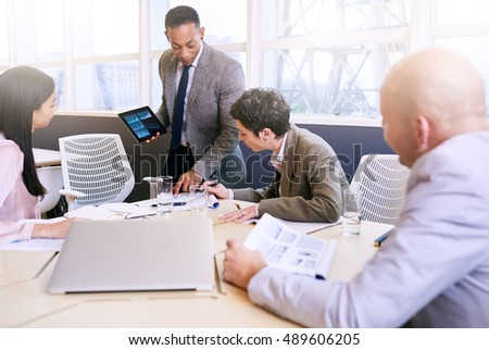 Professional mature adult mixed race well dressed businessman conducting a presentation in a bright modern conference room while holding and using a tablet in his presentation.