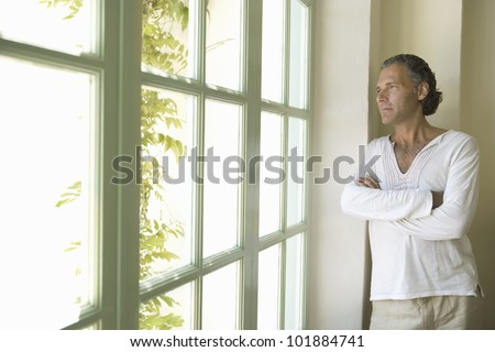 Professional mature man at home looking out a large window into a sunny day.