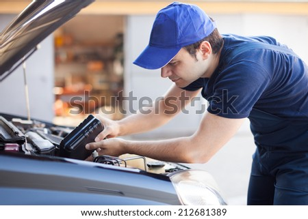 Professional mechanic servicing a car engine - stock photo