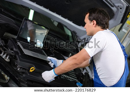 Professional mechanic using a laptop computer to check a car engine - stock photo