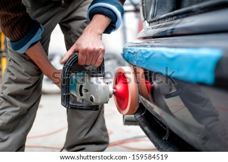 professional mechanic using a power buffer machine for cleaning the body of a car from scratches. Detail of car care concept - stock photo