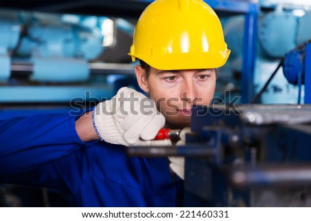 professional mechanic working in factory - stock photo