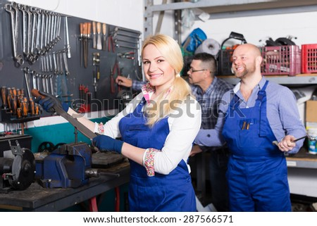 Professional mechanics near stand tools at workshop. Focus on woman
