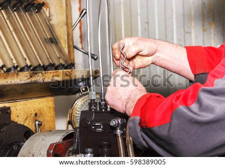 Professional mechanics testing diesel injector in his workshop, repair of diesel fuel injectors, ustroustvo for the diagnosis of fuel injectors soft focus