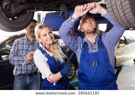 Professional mechanics with supervisor near car at workshop. Focus on man - stock photo