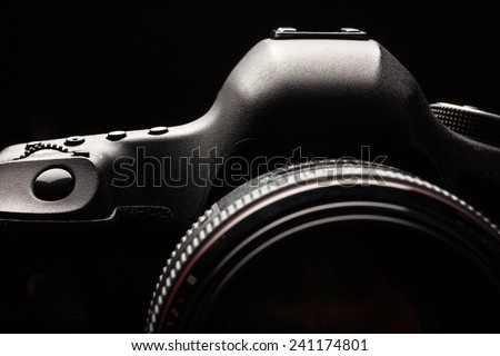 Professional modern DSLR camera low key image - Modern DSLR camera with a very wide aperture lens on - stock photo
