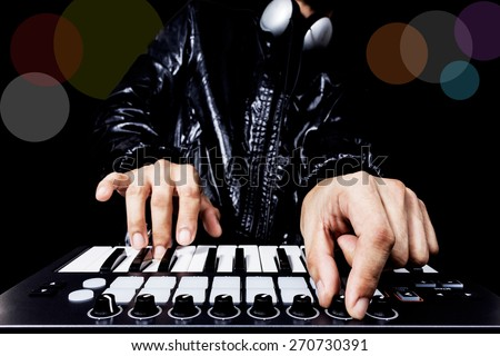 professional musician or DJ hand on studio keyboard synthesizer, colorful bokeh & isolated on black for dance , groove, remix, underground music background concept - stock photo