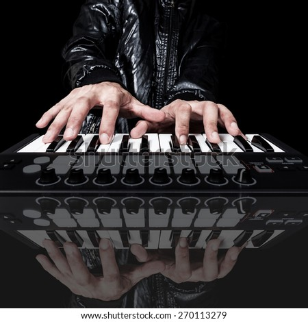 professional musician or DJ hand on studio keyboard synthesizer & reflection, isolated on black for dance , groove, remix, underground music background concept - stock photo
