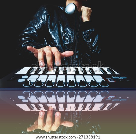 professional musician or DJ hand on studio keyboard synthesizer, reflection & isolated on black for dance , groove, remix, underground music background concept - stock photo