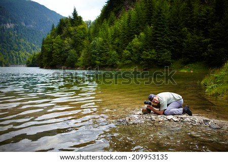 Professional nature photographer outdoor at a lake - stock photo