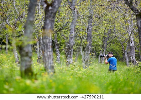 Professional nature photographer shooting with a telephoto lens - stock photo