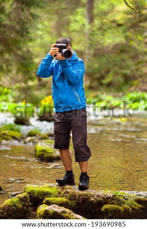 Professional nature photographer taking photos by the river side