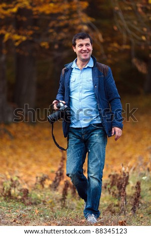 Professional nature photographer taking photos in the forest in an autumn day - stock photo