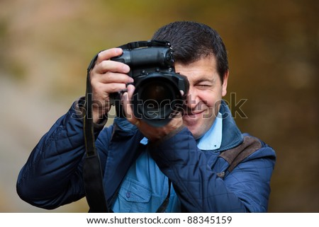 Professional nature photographer taking photos in the forest in an autumn day