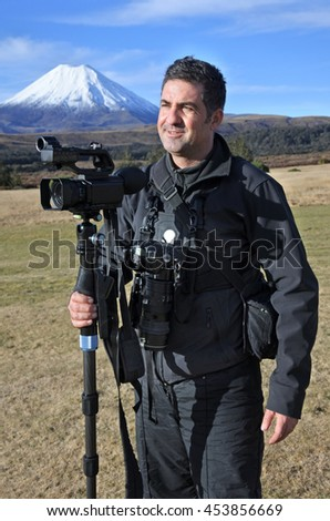 Professional nature, wildlife and travel videographer/photographer photographing Mount Ngauruhoe outdoors during on location photo assignment in Tongariro National Park New Zealand. copy space. - stock photo