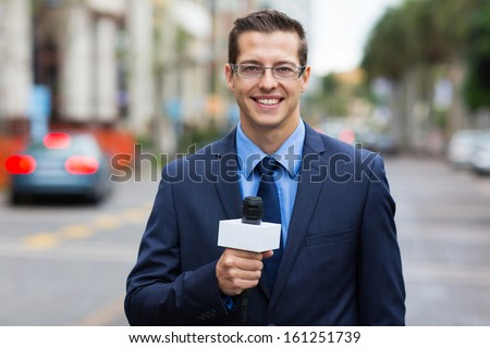 professional news reporter live broadcasting on urban street - stock photo