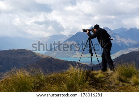 Professional on location and nature photographer (man) photographing landscape  outdoor. - stock photo