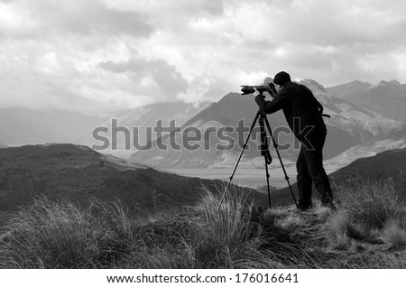 Professional on location and nature photographer (man) photographing landscape  outdoor. (BW) - stock photo