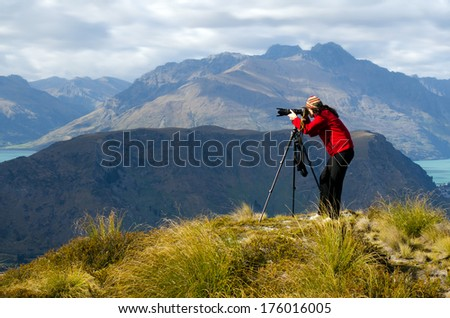 Professional on location and nature photographer (woman) photographing landscape  outdoor. - stock photo