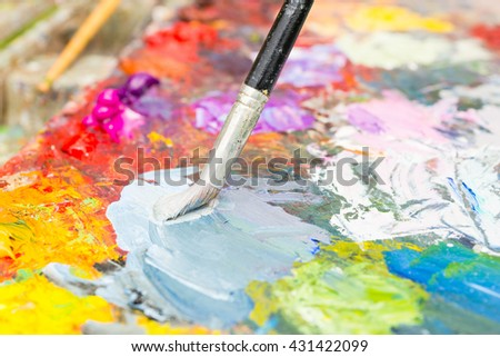 Professional paintbrush mixing colors on the multicolored palette of blended oil paints - stock photo